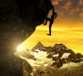 Silhoutte of girl climbing on rock at sunset Royalty Free Stock Photo