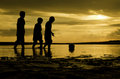 Silhoutte three boys walking toward the ball on water. sunset sunrise and reflection on water Royalty Free Stock Photo