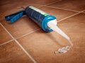 Silicone gun closeup view of a on the floor Royalty Free Stock Photo