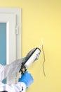 Silicone Sealant Gun fills crack on wall