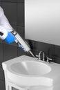Silicone sealant gun, tiles and Sink in a bathroom