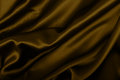 Silk background golden texture dark wavy glossy drapery Royalty Free Stock Photography