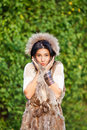 Silly girl beautiful young woman in a fur coat making faces Stock Photography