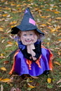 Silly little girl in witch costume with face hands Stock Photos