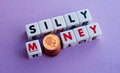 Silly money text and inscribed on small white cubes with letter o replaced by pile of pennies purple background Stock Images