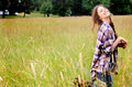 Silly teen girl a pretty teenage with long brown braided hair recreating in a field of tall grass wearing a blue plaid shirt Stock Image
