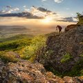 Silouette od photographer in nice mountain sunset with green forest Royalty Free Stock Photo