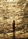Silouette of young girl in front of sea brightly lighted Royalty Free Stock Images