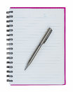 Silver ball point pen on pink notebook isolated white background Royalty Free Stock Photo