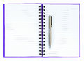 Silver ball point pen on purple notebook isolated white background Royalty Free Stock Photo