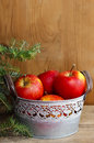 Silver bucket of red apples on wooden table fir branches in the background Stock Photo