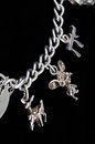 Silver charms on chain section of a sterling charm bracelet against a black background Stock Image