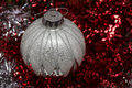 Silver Christmas ball on red sparkly background Royalty Free Stock Photo