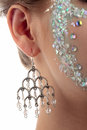 Silver earring close up of a hanging on the ear of a girl with diamond make up on a white background Stock Image