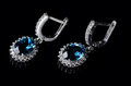 Silver earrings with blue topaz  on a black background. Royalty Free Stock Photo