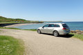 Silver estate car in sunny panoramic view with road, beach, sea. Royalty Free Stock Photo