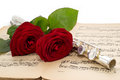 Silver flute and beautiful red rose on an ancient music score