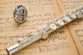 Silver flute and pocket metronome  on an ancient music score Royalty Free Stock Photo