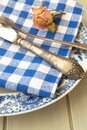 Silver fork and knife with an empty vintage plate on a blue napkin, with dry rose Royalty Free Stock Photo