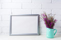 Silver landscape frame mockup with maroon purple flowers in mint Royalty Free Stock Photo