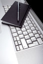 Silver lap top and black pocket planner Royalty Free Stock Photo