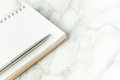 Silver metal pen on blank notebook page on marble desk Royalty Free Stock Photo