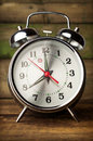 Silver retro alarm clock close up on wooden background Stock Photos