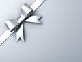Silver ribbon bow on corner gray background white or Royalty Free Stock Images