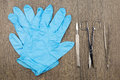 Silver scalpel surgical scissors and forceps beside blue latex glove Royalty Free Stock Photo