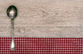 Silver spoon on old wooden board checkered table cloth and Stock Photos
