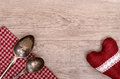 Silver spoon and table cloth with heart on a wooden board Stock Photo