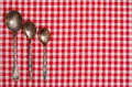 Silver spoons on a checkerd cloth table Royalty Free Stock Photo