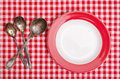 Silver spoons and red plate three on a checked table cloth Stock Photography