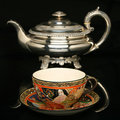 Silver teapot and an antique chinese cup of tea Royalty Free Stock Photo