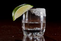 Silver tequila shot served in a small glass with a lime wedge and salt on the rim Stock Photo