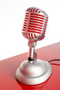 Silver vintage microphone with red membrane on a red white background Stock Photo