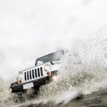 Silver wd crossing stream dramatic action shot of modern unmarked sport utility vehicle making splash while river Stock Photos
