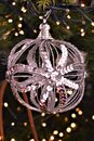 Silver white sparkling ornament hanging from greenery and surrounded by lights. Royalty Free Stock Photo