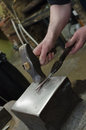 A silversmith is forging an hot piece of silver with a hammer Royalty Free Stock Photography