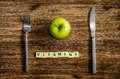 Silverware and apple set on wooden table with sign Vitamins Royalty Free Stock Photo