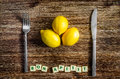 Silverware and lemons on wooden table with bon apetit sign vintage Stock Photo