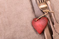 Silverware and red wooden heart on gray cloth background Royalty Free Stock Photo
