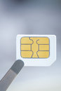 Sim card for smart mobile phone with tweezer close up Royalty Free Stock Image