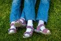 Similar legs in sandals of twin girls closeup shot Royalty Free Stock Image