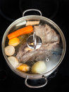 Simmer of beef broth with seasoning vegetables boiling in stew pan on glass ceramic cooker Stock Images