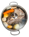 Simmer of beef broth in steel pan with seasoning vegetables isolated on white background Royalty Free Stock Photo