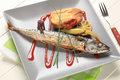 Simple baked mackerel recipe roasted whole with potato and raspberry balsamic reduction Royalty Free Stock Photo