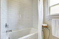 Simple bathroom with tile wall trim and bath tub Royalty Free Stock Photo