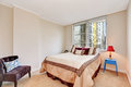Simple beige bedroom interior with brown and creamy tones bed.