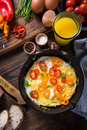 Simple classic brunch scrambled eggs in rustic pan on wooden table Stock Photography